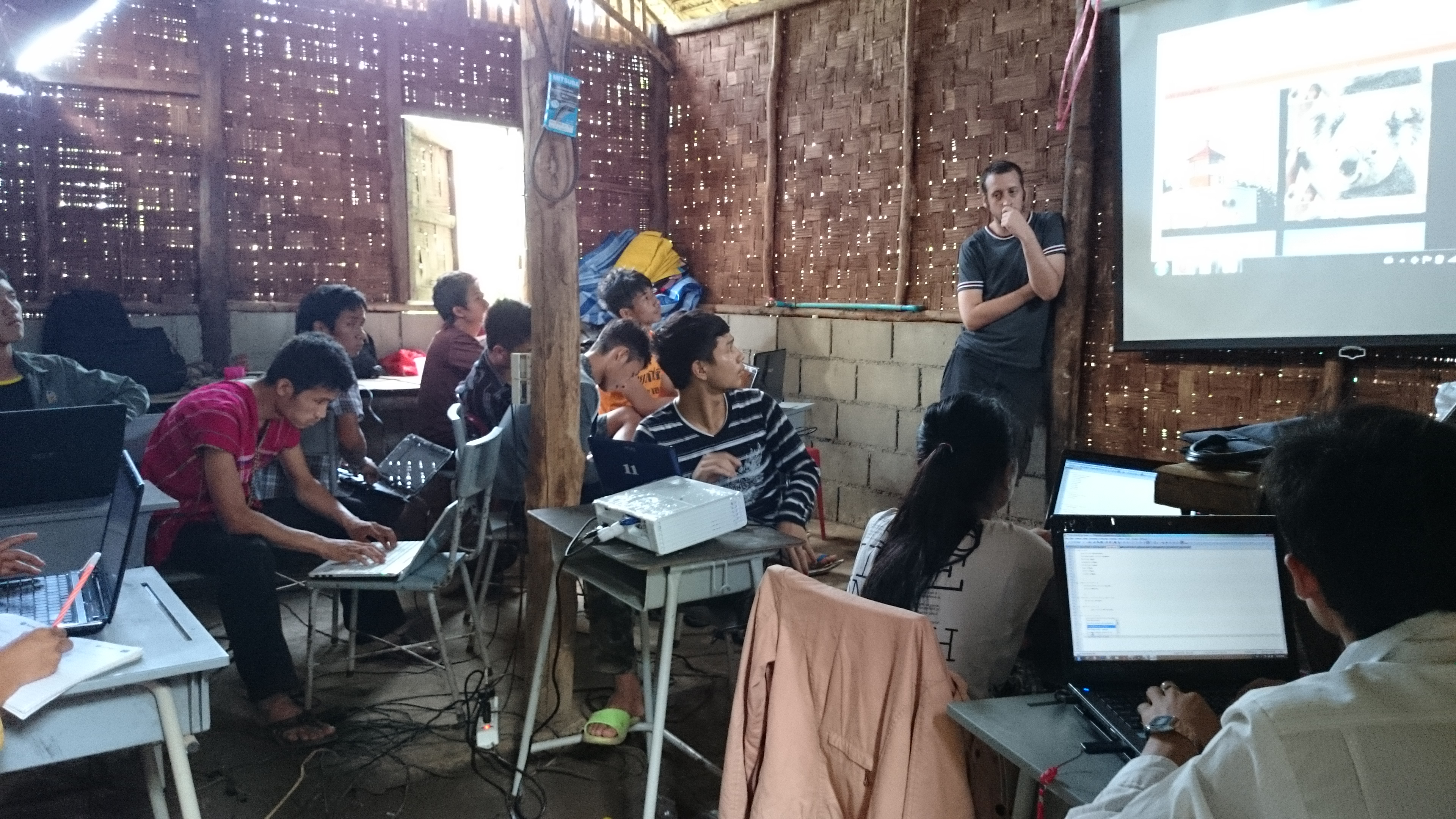 Pierre and his Karen refugee students focusing on their code